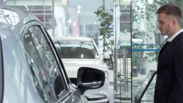 Young businessman in a suit examining cars for sale at the dealership