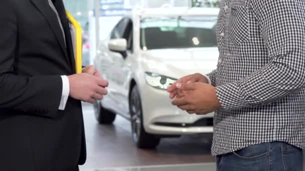 Car dealer shaking hands with client and passing car keys to the man
