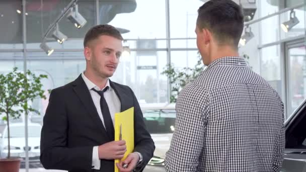 Car salesman giving car keys to the customer after shaking hands