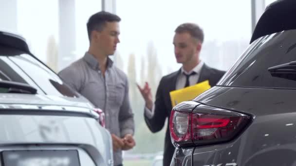 selektiver Fokus auf ein Auto, männlicher Kunde im Gespräch mit Autohändler im Hintergrund