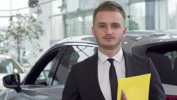 Professional car salesman holding car key, looking to the camera confidently