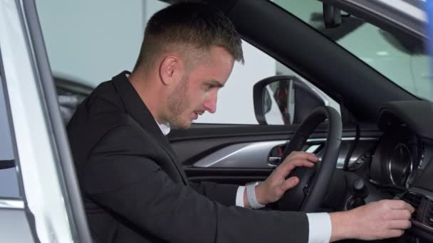 Businessman sitting in a new car, checking out interior of a vehicle