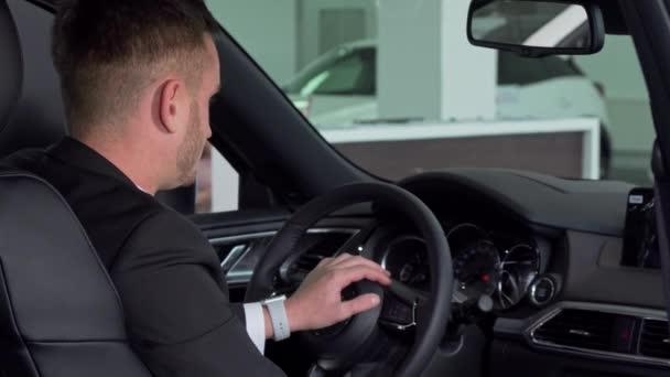 Vousatý podnikatel podal klíč od auta do kamery, sedící v novém automobilu