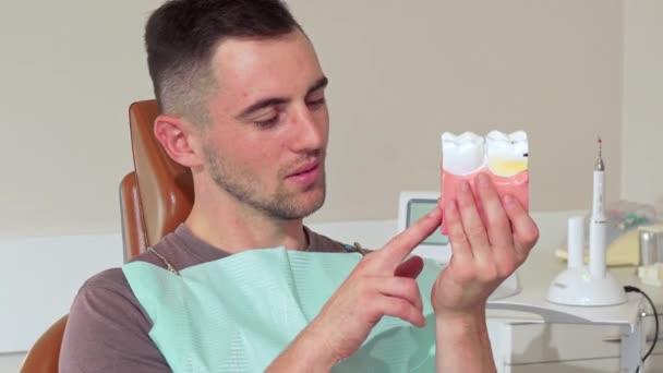 Hübscher junger Mann lächelnd in die Kamera hielt dental Schimmel in der Klinik