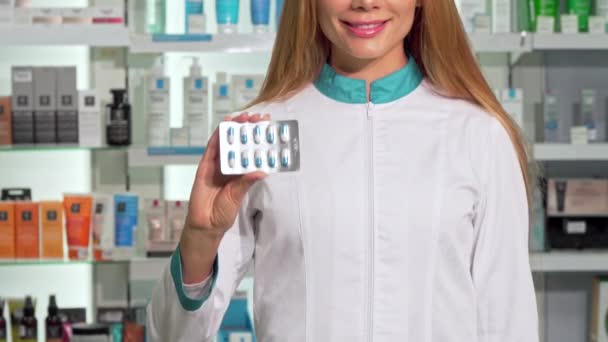 Smiling female pharmacist holding out blister of pills to the camera. Cropped shot of a happy chemist working at the drugstore, holding vitamins pack. Retail, medical concept