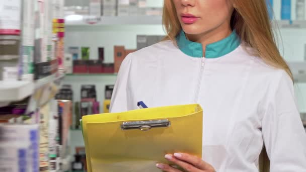 Unrecognizable female pharmacist writing on clipboard at drugstore