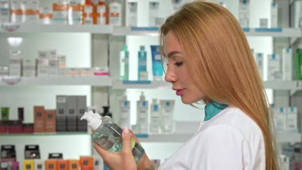 Female pharmacist smiling to the camera, holding two medication bottles