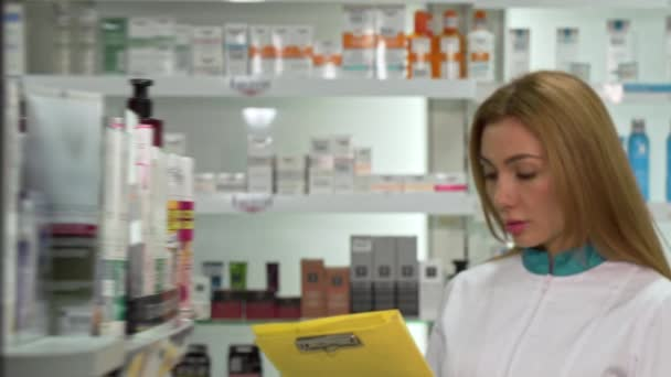 Young female pharmacist walking in the drugstore, checking products in a list. Lovely female chemist working at pharmacy, filling papers on clipboard. Occupation, medical industry concept