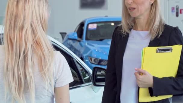 Female customer receiving car keys, shaking hands with saleswoman