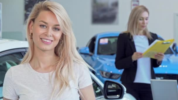 Gorgeous happy woman smiling, holding car keys after buying new auto. Attractive female driver buying new vehicle, professional car dealer on the background. Consumerism, rental concept