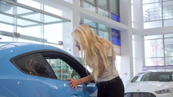 Stunning female customer smiling to the camera, examining new car at dealership