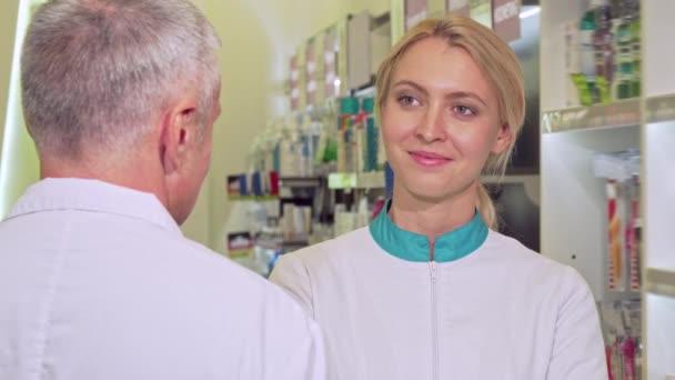 Die schöne Chemikerin lächelt fröhlich und spricht mit ihrem älteren Kollegen
