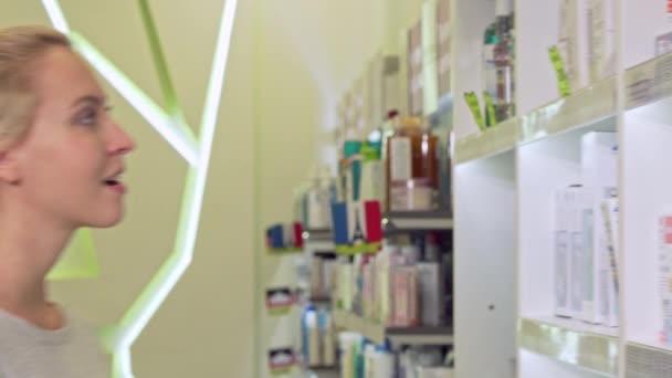 Szép fiatal nő mosolyog a kamerába, bevásárlóközpont, gyógyszertár