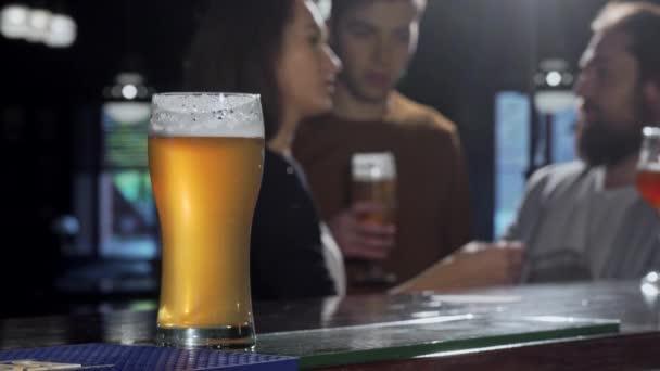 Selektivní fokus na sklenku piva, lidé pití v hospodě na pozadí