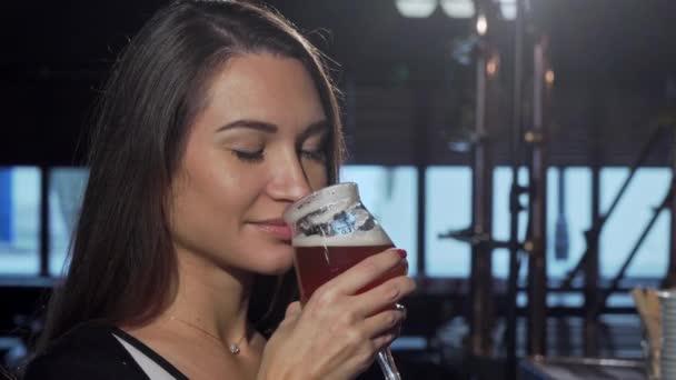 wunderschöne Frau riecht und trinkt köstliches Bier in der Kneipe
