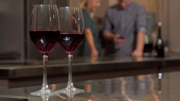Sklenice na víno na stole, pár pomocí chytrého telefonu společně doma na zadní straně