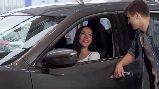 Gorgeous woman sitting in a new car at dealership, talking to her boyfriend