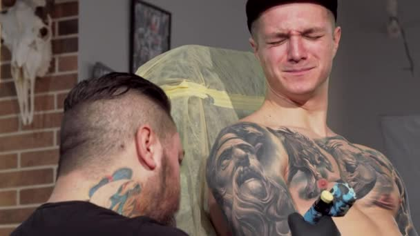 Young man getting painful tattoo on his arm