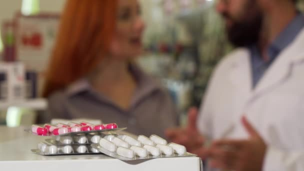 Pharmacist taking blister of pills from the counter, talking to his female customer