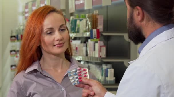 Beautiful woman receiving pills from her pharmacist, shopping at drugstore