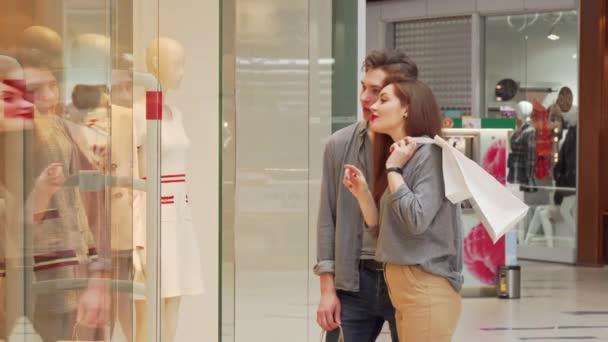 Šťastný mladý pár nakupující společně, zkoumáním oblečení na displeji obchodu