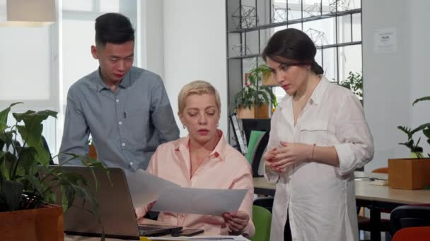Mature female CEO talking to her workers at the meeting room