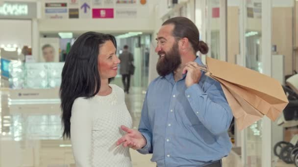 Bearded handsome man and his lovely wife looking inside shopping bags