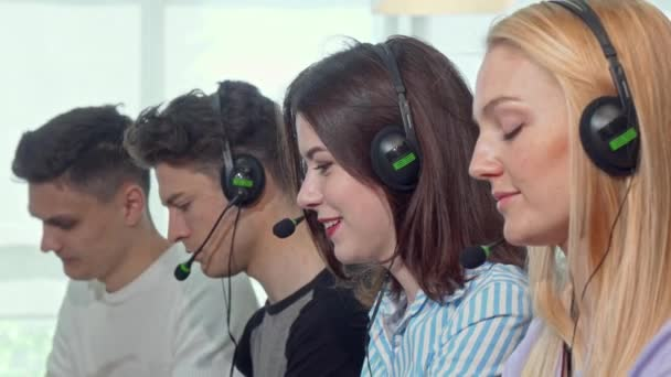Group of young people wearing headsets, working at call center