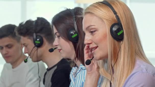 Charming female call center operator smiling to the camera while working