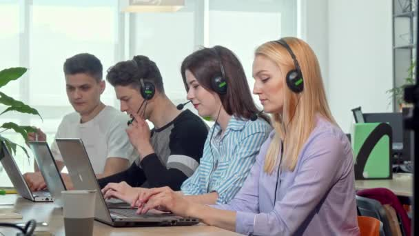 Beautiful young woman answering calls, working at customer support call center