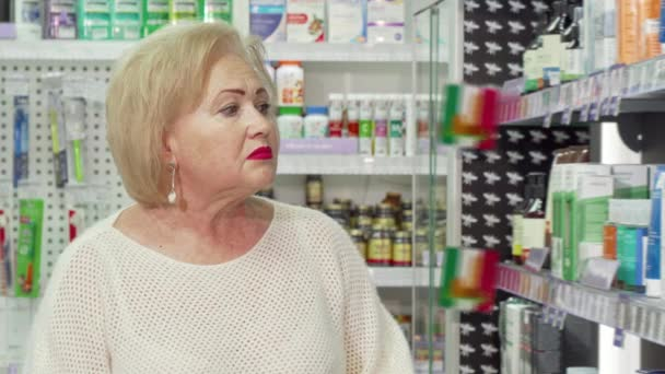 Charming senior woman smiling to the camera, shopping at drugstore
