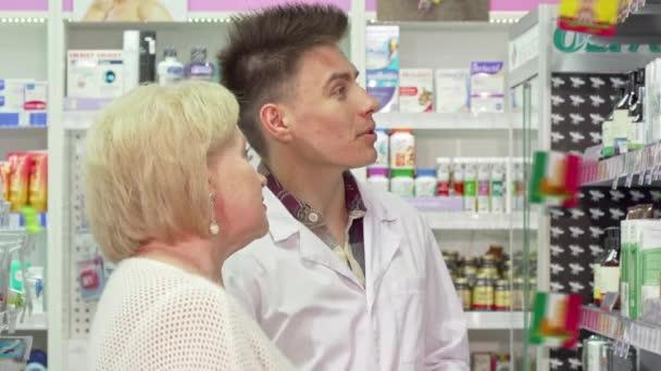 Cheerful male pharmacist helping elderly female customer