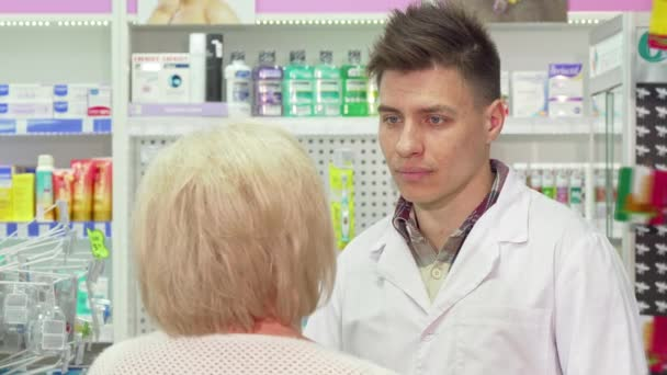 Young male pharmacist talking to his elderly client