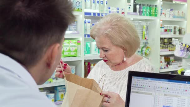 Senior woman buying medical products at pharmacy, looking in a shopping bag