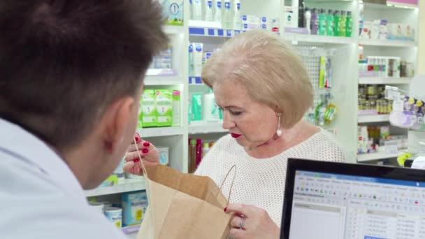 Seniorin kauft Medikamente in Apotheke und schaut in Einkaufstasche