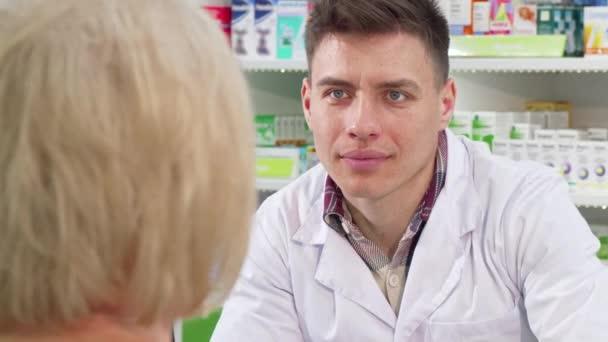 männlicher Chemiker hört seiner älteren Kundin zu, was die Medizin angeht
