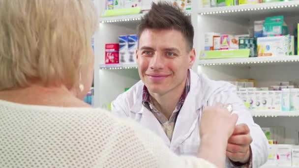 Cheerful pharmacist selling medication to senior customer