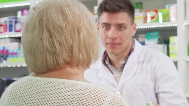 Rückansicht einer Seniorin, die nach dem Kauf von Medikamenten in die Kamera lächelt