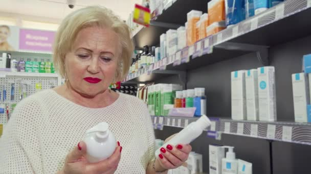 Lovely senior woman smiling, choosing between two products at the drugstore