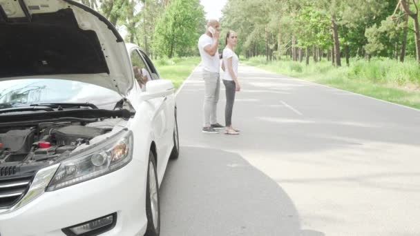Couple calling tow truck service standing on the road with broken car