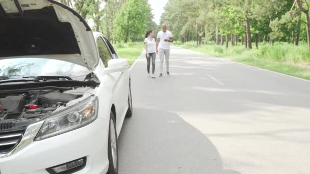Couple waiting for tow truck service on countryside road