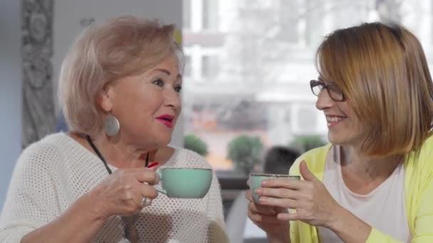 Starší matka chatuje se svou dcerou nad šálkem kávy v kavárně