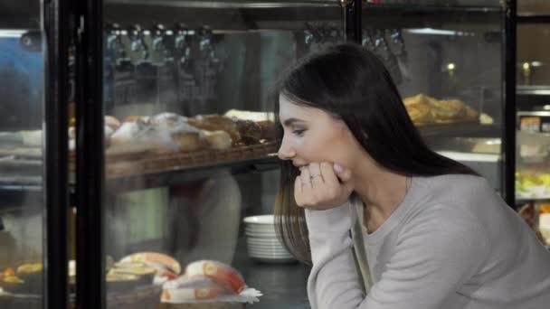 Krásná mladá žena vybírá dezert z displeje v kavárně