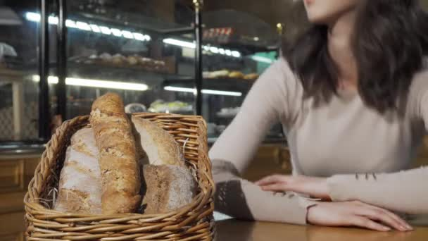 Beautiful woman smelling freshly baked bread in a basket at bakery store