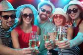 Šťastná skupina mladých přátel dotýkající se sklenic s sebou