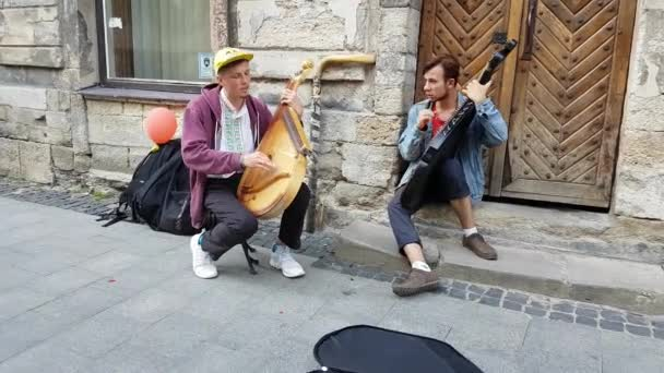 Lviv, Ukraine - July 16, 2019: Young bandura players playing the traditional Ukrainian musical instrument bandura on city street.