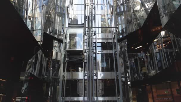 Londýn, Velká Británie - 13 září 2018: moderní skleněný výtah na straně moderní nákupní centrum v centru Londýna poskytuje klasickým příkladem architektury Bowellism. Abstraktní linie a odrazy, pomalý pohyb