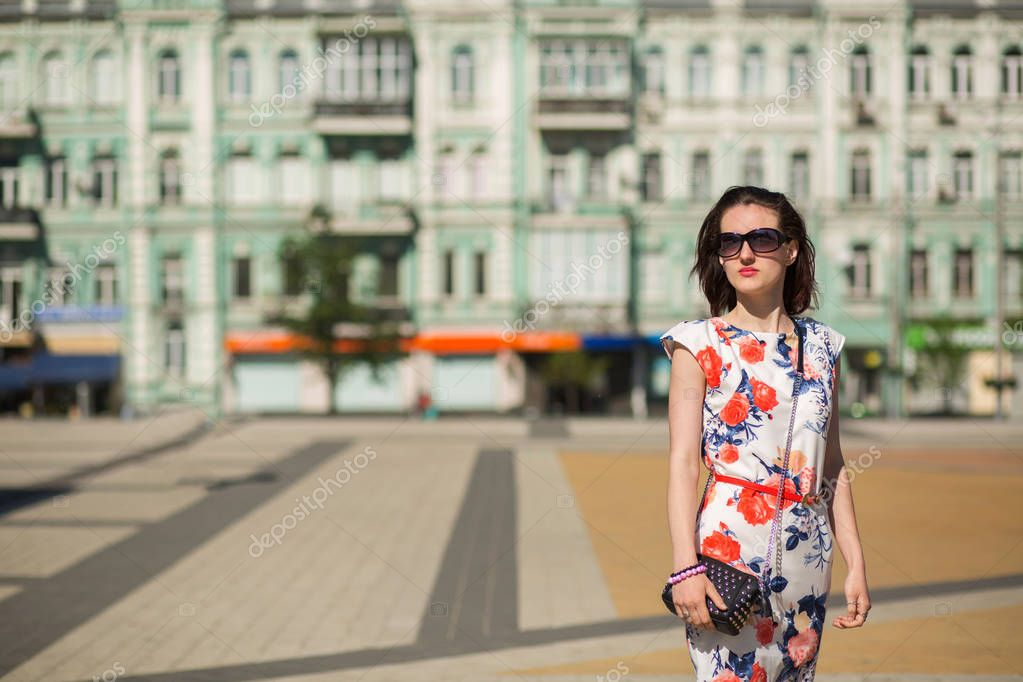 Wonderful brunette woman wearing trendy dress and glasses, posing at the street. Empty space