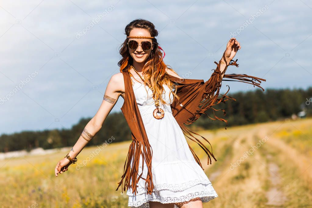 portrait of young hippie girl with feathers in long hair posing outdoors
