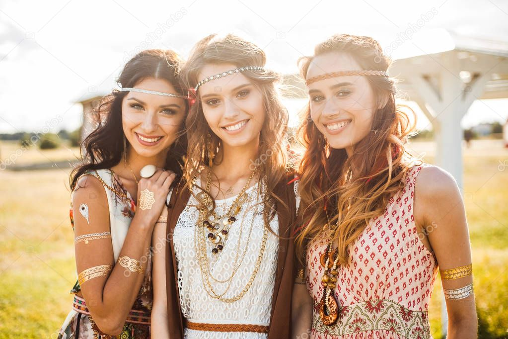 Three hippie girls in dresses posing on nature background